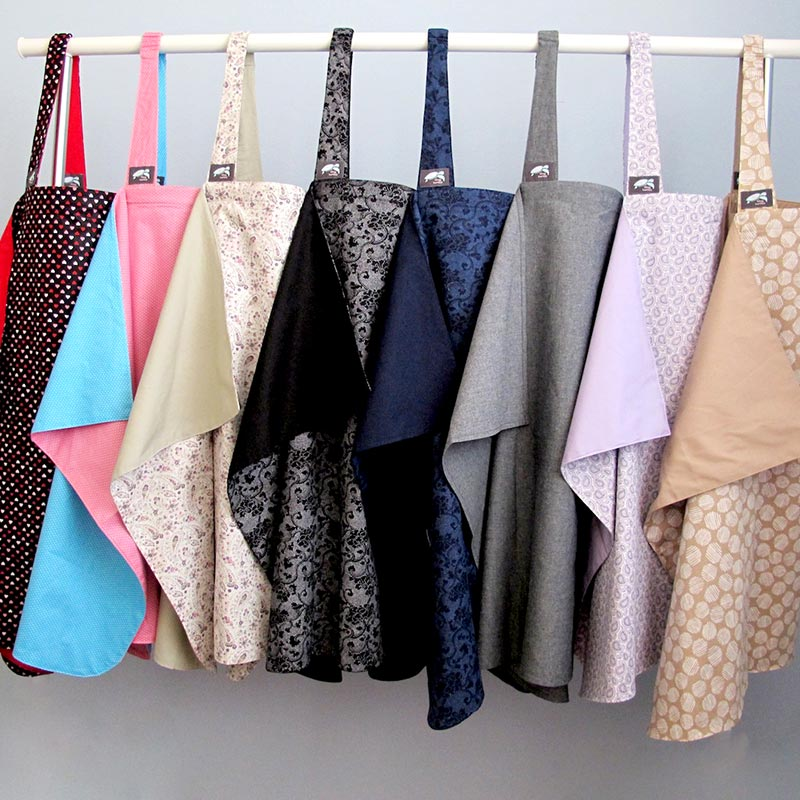 different colours of nursing cover all hanging on a rail